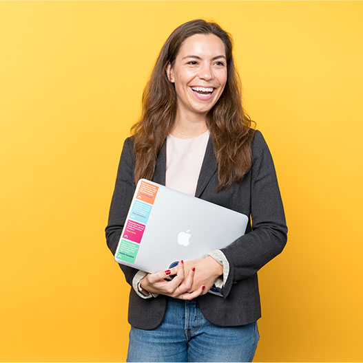 woman holding laptop in front of yellow wall
