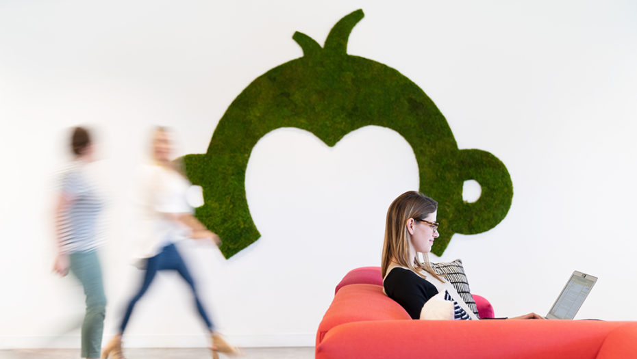 Surveymonkey logo design on wall with motion blurred people walking by